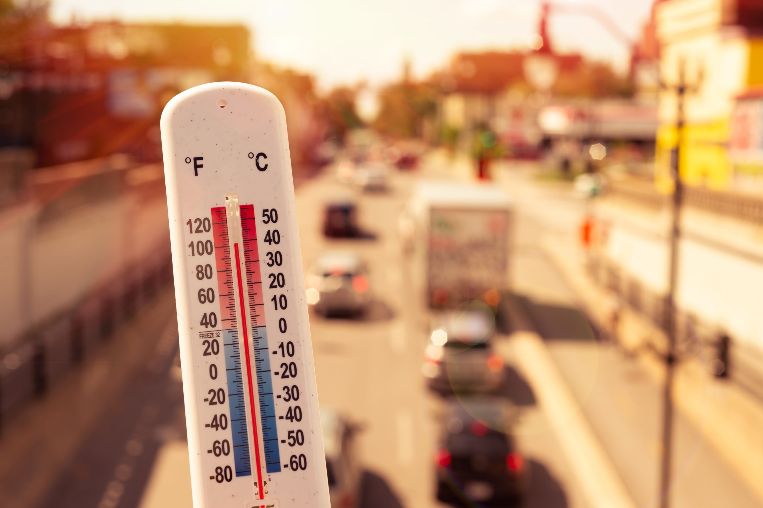 Thermometer in front of cars and traffic during heatwave in the City.